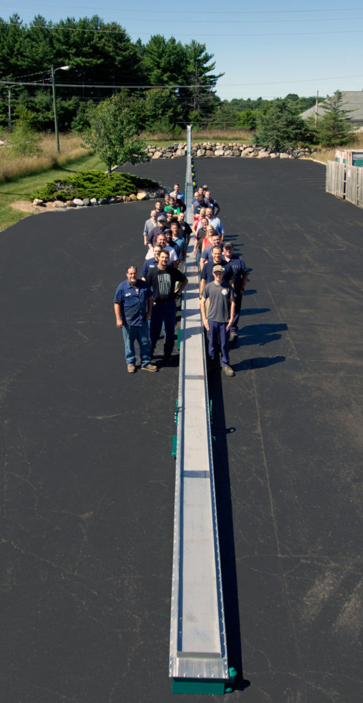 MPI Employees with 224 foot beltless magnetic conveyor